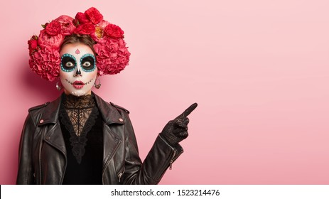 Studio shot of emotive gothic woman has image of horror dead woman, wears skull makeup, wreath around head and black leather jacket, points away, shows direction with stupor. Scarying girl indoor