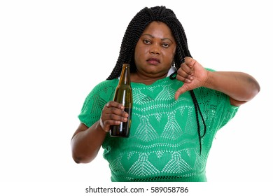 Studio shot of fat black African woman holding bottle of beer and giving thumb down