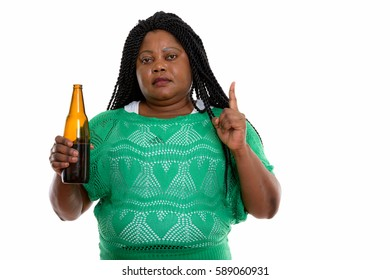 Studio shot of fat black African woman holding bottle of beer and pointing finger up