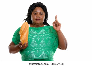 Studio shot of fat black African woman holding bread and pointing finger up