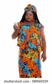 Studio shot of fat black African woman standing and using mobile phone while wearing traditional clothes