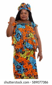 Studio shot of fat black African woman standing while wearing traditional clothes and looking motivated