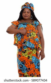 Studio shot of fat black African woman standing while wearing traditional clothes and giving thumb up