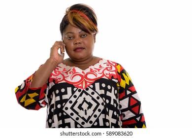 Studio shot of fat black African woman talking on mobile phone