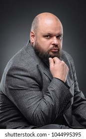 Studio shot of fat businessman thinking against gray background. Cute adult man in a gray suit.
