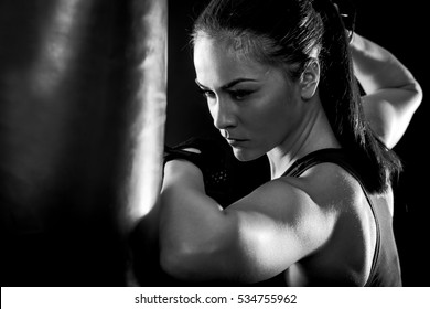 Studio shot of female boxer punching a boxing bag with elbow, Black and white.