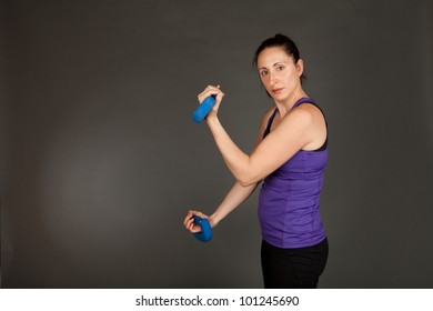 Studio shot of a fit brunette woman lifting weights on a grey background