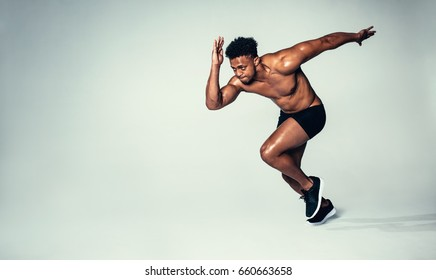 Studio shot of fit young man running over grey background. African american male model with muscular body.