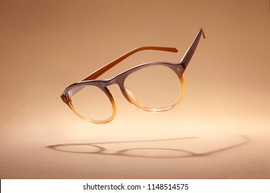 Studio shot of flying brown glasses with shadow on beige background.