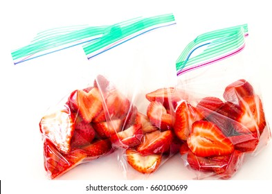 Studio shot fresh chopped strawberries in three clear plastic bag with lock isolated on white. In-house cut, packed strawberry in transparent zipper bags to-go/take away. Convenience, healthy concept.