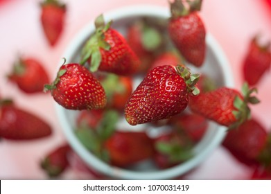 Studio shot of fresh strawberries falling into a bowl from top view with shallow depth of field