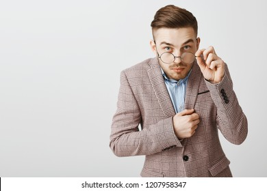 Studio shot of funny nerdy male office worker in trendy jacket with trendy hairstyle looking from under glasses touching rim of eyewear being intrigued and interested while hearing secret of friend