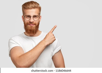 Studio shot of ginger hipster with thick beard, trendy haircut, has serious expression, points with index finger at upper right corner, dressed in white t shirt shows free space for your advertisement