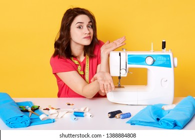 Studio shot of girl seamstress sitting at white desk with sewing machine, spreding hands, does not know how to switch it. Attractive brunette sewer looks at camera and shrugging. Sewing concept.