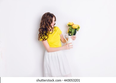 A studio shot of a girl standing and holding a white vase with flowers. The girl has long wavy brunette hair and wears a yellow t-shirt and white skirt. Girl smiles widely and looks at the flowers.