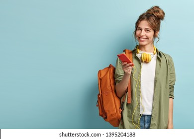 Studio shot of glad female model holds modern smartphone gadget, reads publication and listens audio message in headphones, wears casual long shirt and jeans, carries rucksack, smiles positively