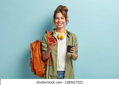 Studio shot of glad female student has coffee break after lectures, listens audio book in headphones, enjoys record from website, uses mobile phone for chatting online, has rucksack on back.