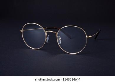 Studio shot of gold glasses at dark background.