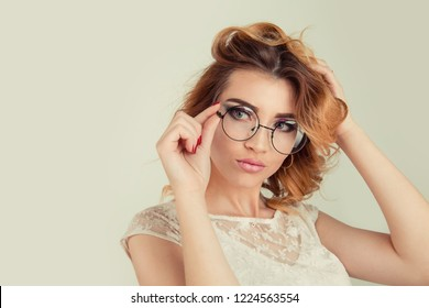 Studio shot of good looking blonde curly female woman looking to the side wearing big round spectacles touching her eyeglasses posing isolated on light yellow green background Bob hairstyle with curls