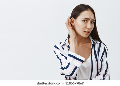 Studio shot of good-looking gloomy girlfriend with long dark hair, leaning towards camera with one ear and gazing at camera, eavesdropping and whispering, hearing rumor, feeling nervous