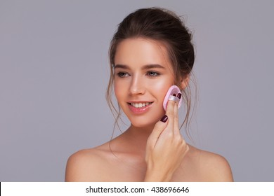 Studio shot of a gorgeous girl applying face powder