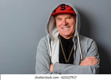 A studio shot with a gray wall behind a man. Funny grandad gives a smile. A red cap, a gray hoodie and a black t-shirt with a gold chain on it make this grandpa look younger.
