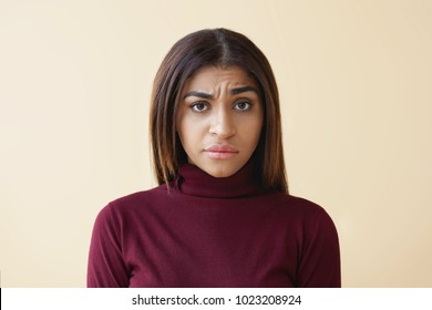 Studio shot of grumpy frowning mixed race girl with straight dark hair staring at camera with suspicious skeptical expression while listening to some silly excuses, suspecting husband of adultery