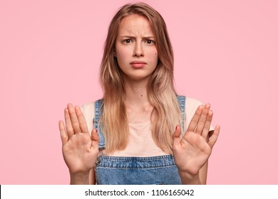 Studio shot of grumpy young female with irritated expression, makes stop gesture and keeps palms in front, asks to stop panic and be quiet, stands against pink background. Body language concept