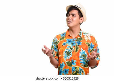 Studio shot of handsome Asian man looking upset isolated against white background