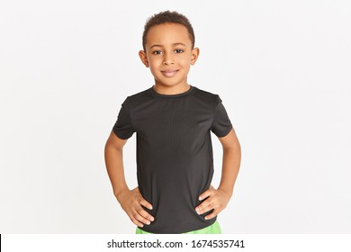 Studio shot of handsome athletic dark skinned little boy posing isolated in black t-shirt keeping hands on his waist, training indoors. Children, sports, fitness, healthy and active lifestyle concept