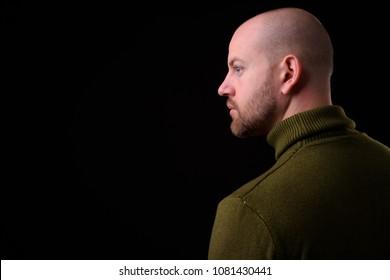 Studio shot of handsome bald bearded man against black background