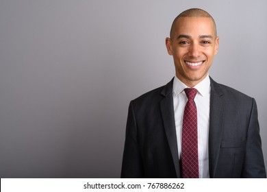 Studio shot of handsome bald businessman wearing suit against gray background