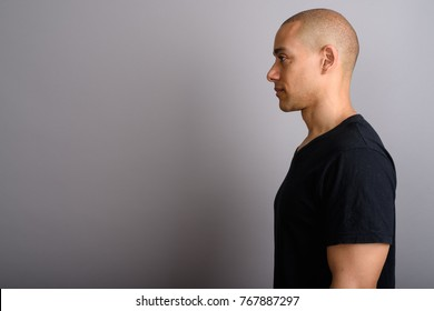 Studio shot of handsome bald man wearing black shirt against gray background