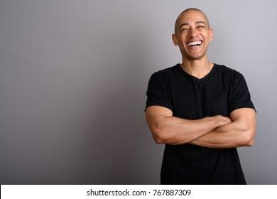 Studio shot of handsome bald man wearing black shirt against gray background