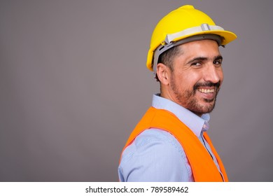 Studio shot of handsome bearded Persian man construction worker against gray background