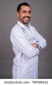 Studio shot of handsome bearded Persian man doctor against gray background
