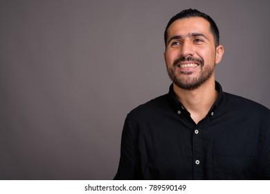 Studio shot of handsome bearded Persian man wearing black shirt against gray background