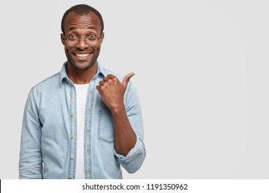 Studio shot of handsome cheerful dark skinned man with toothy smile, shows new item, has shining teeth, dressed in fashionable clothes, poses agaist white background with copy space for your text