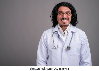 Studio shot of handsome man doctor with mustache against gray background