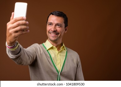 Studio shot of handsome man using mobile phone against brown background