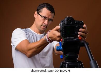 Studio shot of handsome man vlogging against brown background