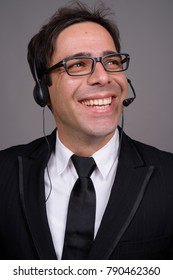 Studio shot of handsome Persian businessman working as call center representative against gray background