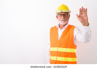 Studio shot of handsome senior bearded man construction worker showing stop hand sign while wearing eyeglasses against white background