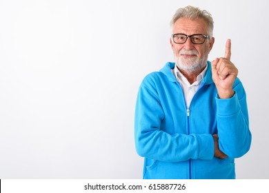 Studio shot of handsome senior bearded man pointing finger up ready for gym against white background