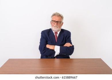 Studio shot of handsome senior bearded businessman with arms crossed while sitting on wooden table against white background