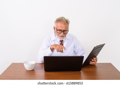 Studio shot of handsome senior bearded man doctor holding clipboard while pointing at laptop on wooden table against white background
