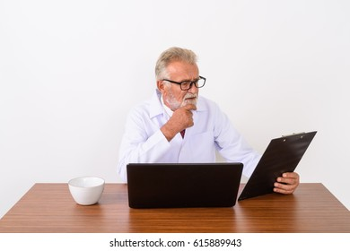 Studio shot of handsome senior bearded man doctor thinking while reading on clipboard with laptop and coffee cup on wooden table against white background