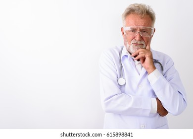Studio shot of handsome senior bearded man doctor thinking while wearing protective glasses against white background