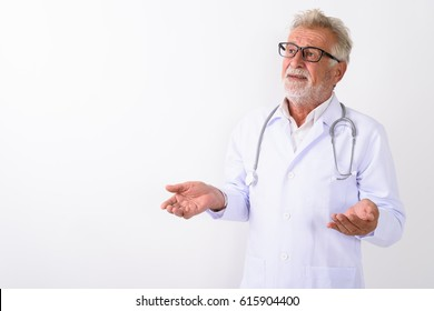 Studio shot of handsome senior bearded man doctor thinking while looking confused against white background