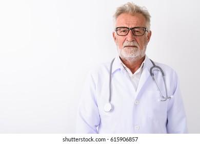 Studio shot of handsome senior bearded man doctor wearing eyeglasses against white background